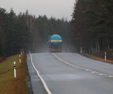A truck tank vehicle driving down a misty road along many green trees